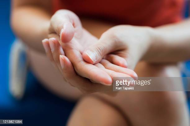 a young southeast asian woman is applying moisturizing lotion on hands - handcrème stockfoto's en -beelden