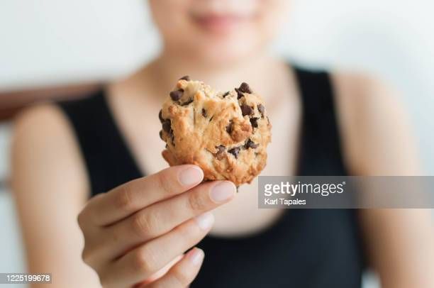 a young southeast asian woman is holding a freshly baked cookie - filipino ethnicity and female not male stock pictures, royalty-free photos & images