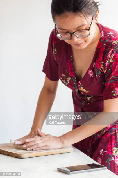 a young southeast asian woman learning to bake online using her mobile phone - filipino ethnicity and female not male fotografías e imágenes de stock