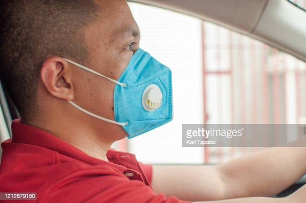 a young southeast asian young male adult is driving a car while wearing face mask - driving mask stock pictures, royalty-free photos & images