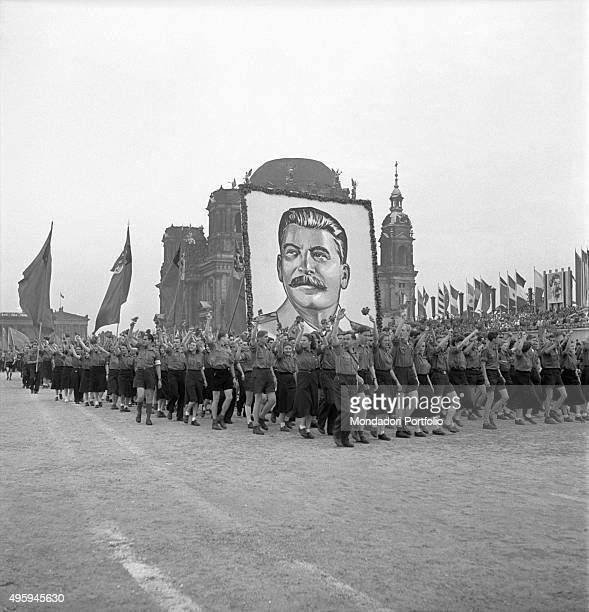 Young Soviet people parading under the image of the chairman of the Communist Party of USSR Joseph Stalin for the World Festival of Youth and...