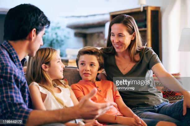 joven familia española juntos en sofá en casa familiar - discusión fotografías e imágenes de stock