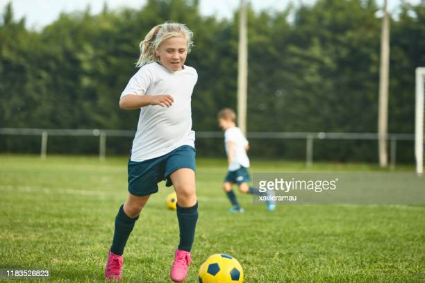 young spanish female footballer practicing dribbling - junior level stock pictures, royalty-free photos & images