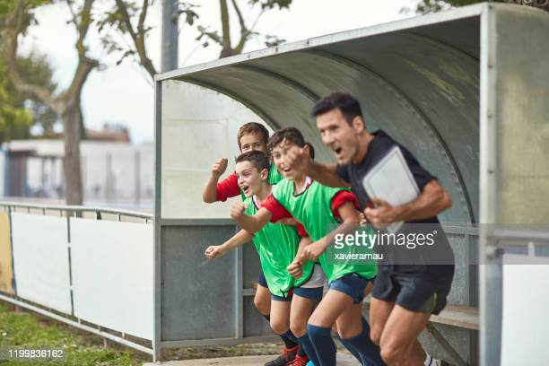 young spanish footballers and coach cheering triumph - sideline stock pictures, royalty-free photos & images
