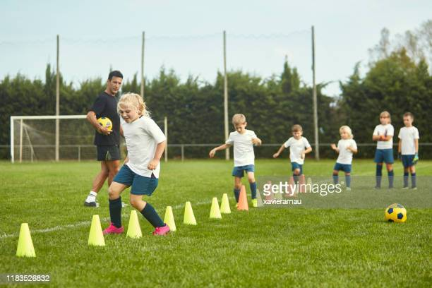 young spanish footballers doing running drills with cones - sports training drill stock pictures, royalty-free photos & images