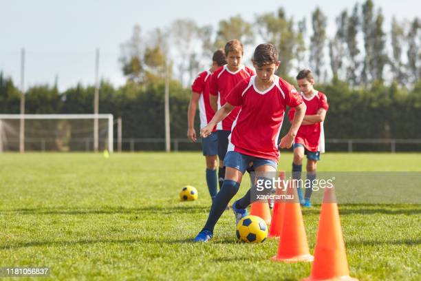若いスペインのサッカー選手は、ドリルでコーンの周りをドリブル - チームスポーツ ストックフォトと画像