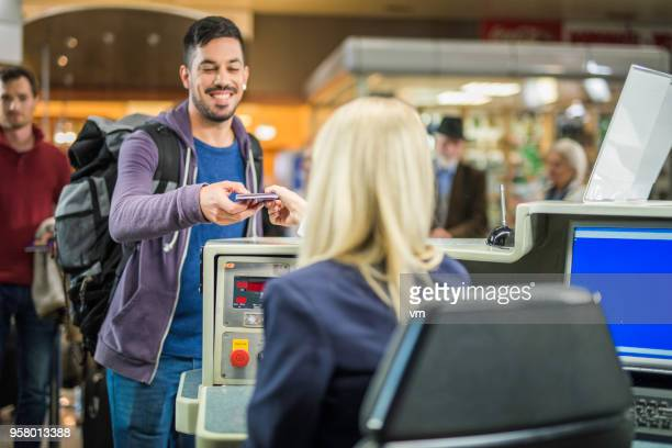 Young spanish man checking in at an airport counter