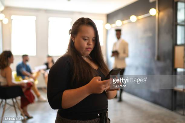 young special needs businesswoman using smartphone at modern startup office - disabilitycollection stock pictures, royalty-free photos & images