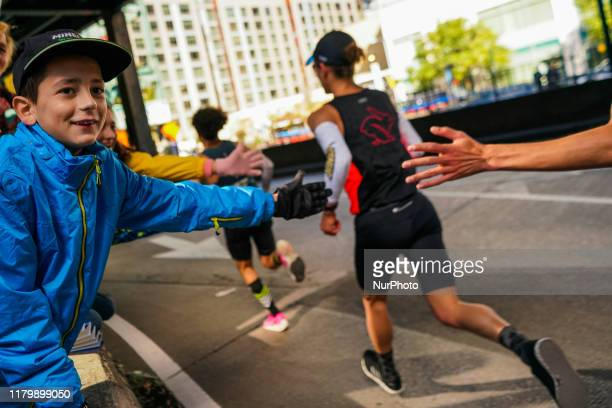 A young spectator high fives runners at the New York City Marathon Sunday November 3rd 2019 The NYC Marathon which is the largest race in the world...