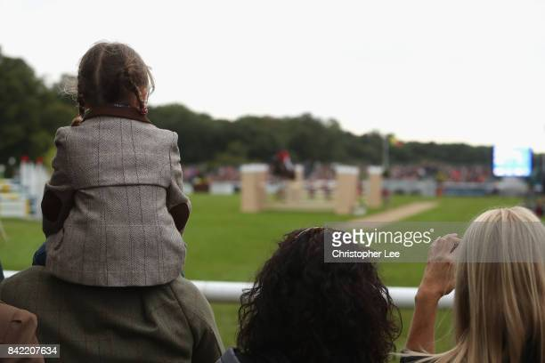 A young spectator sitting her her fathers shoulders watches the riders in action during Day Four of The Land Rover Burghley Horse Trials 2017 on...