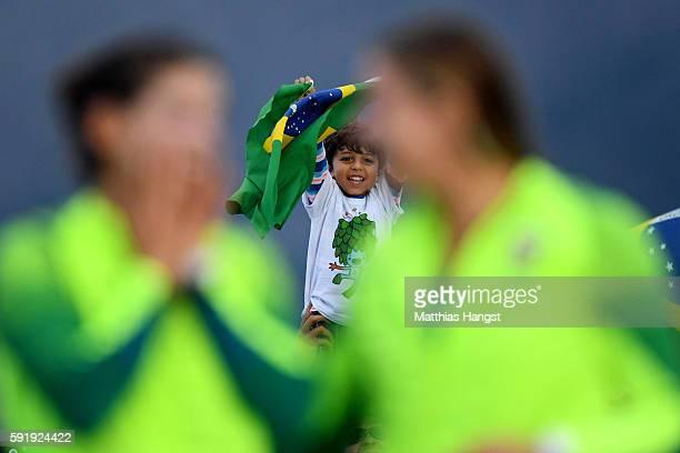 A young spectator watches as Martine Grael of Brazil and Kahena Kunze of Brazil celebrate winning gold in the Women's 49er FX class at the Marina da...