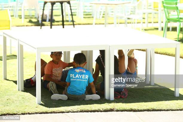 Young spectators congregate under the shade of a table in Garden Square to avoid the hot weather on day four of the 2018 Australian Open at Melbourne...