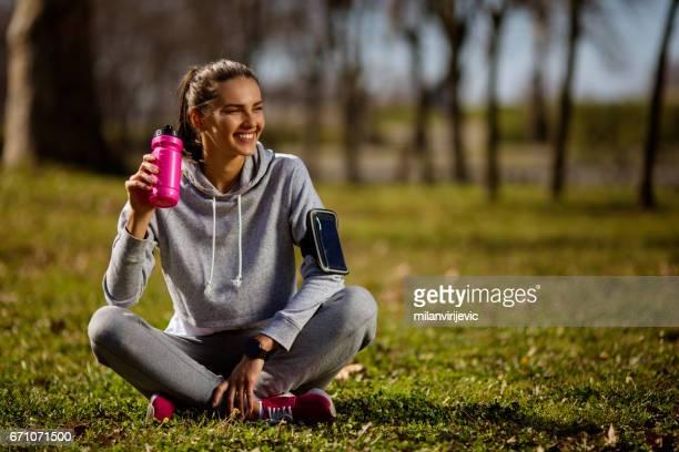 Jeune femme assise sur le terrain de sport