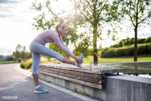 junge sportlerin dehnen vor dem laufen im park. - aufwärmen stock-fotos und bilder