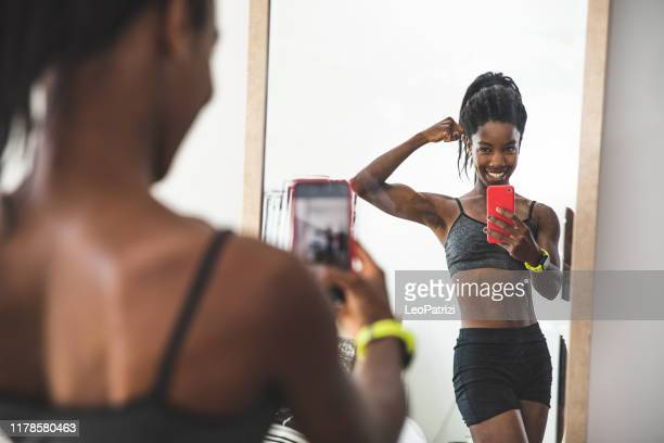 young sportive woman posing for a portrait at home - mirror selfie stock pictures, royalty-free photos & images