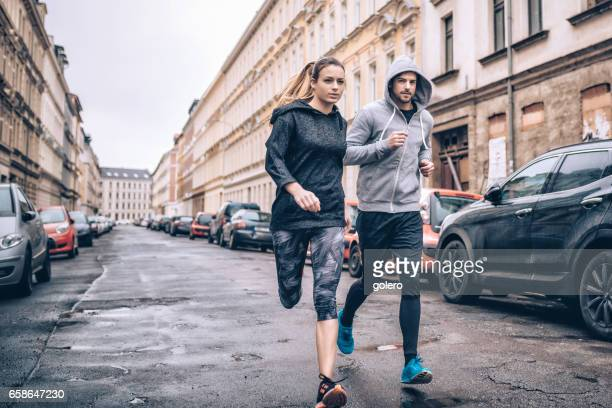 young sports couple running in city streets