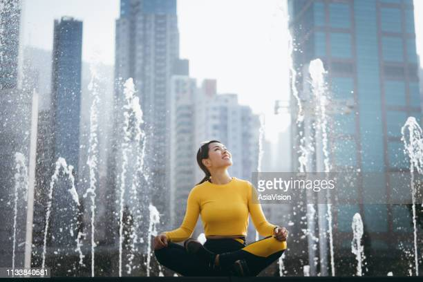 young sports woman meditating in urban park in city, with modern city skyline as background - holy city park stock pictures, royalty-free photos & images