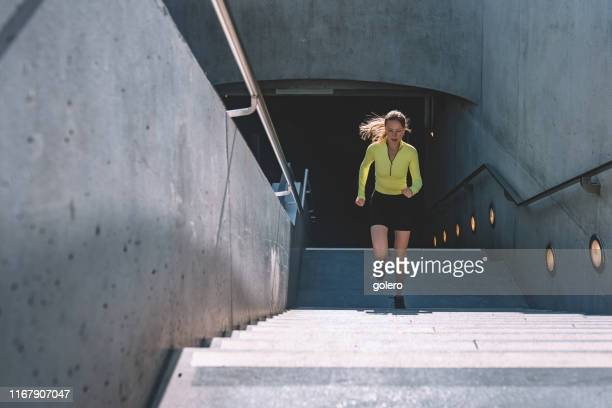 young sports woman running up stairs - fast fashion stock pictures, royalty-free photos & images