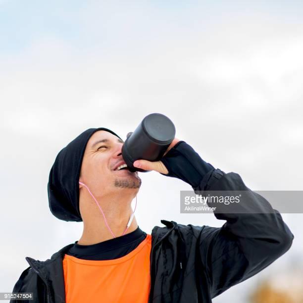 若いスポーツマンの訓練で水を飲む。