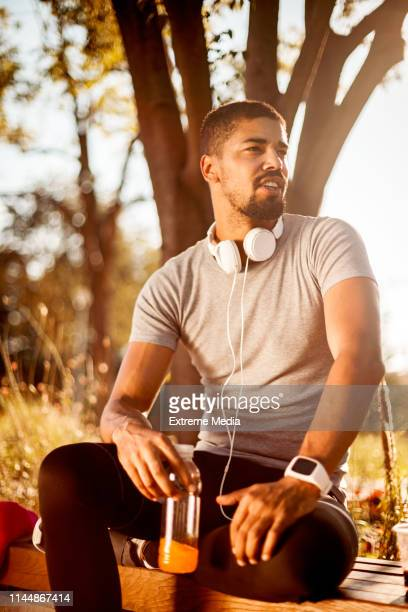 young sportsman hydrating himself with sport beverage while sitting on a park bench and resting from exercising in a public park - energy drink stock pictures, royalty-free photos & images