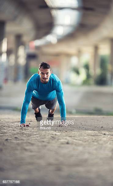 Young sportsman in a plank position on the street.