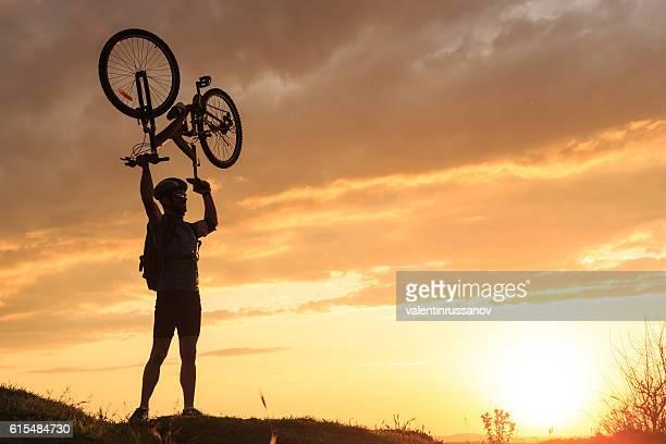 Young sportsman lifting his bike