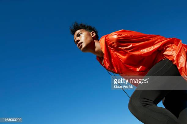 young sportsman looking away against clear blue sky - leuchtende farbe stock-fotos und bilder