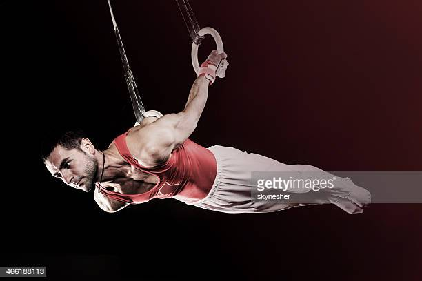 Young sportsman on gymnastics rings.