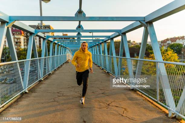 young sportsman running on the bridge - hoodie headphones stock pictures, royalty-free photos & images