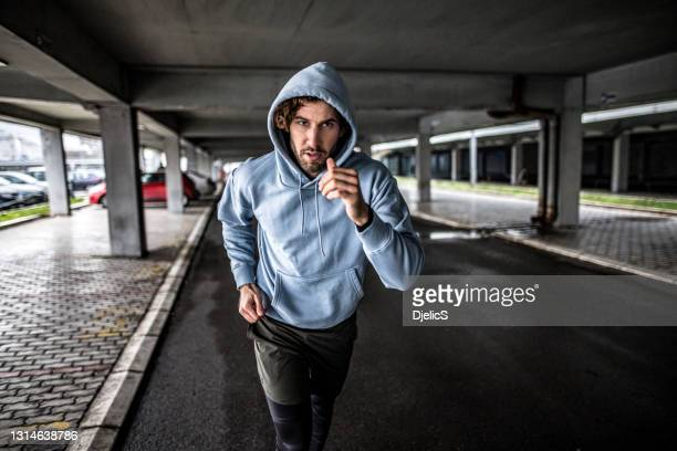 young sportsman running under the bridge. - hooded top stock pictures, royalty-free photos & images