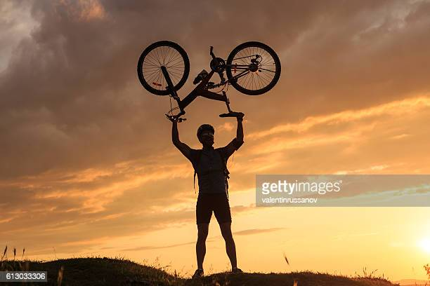 Young sportsman standing on top and lifting his bike