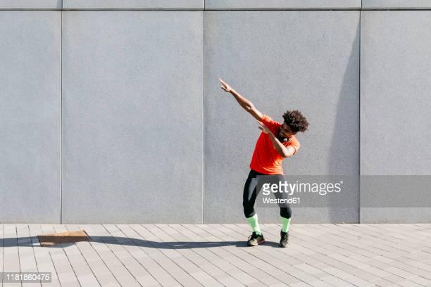 young sportsman with arms raised, listening to music - só um homem imagens e fotografias de stock