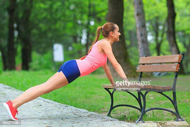 Young sportswoman doing pushups on bench in the park