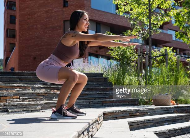jeune sportive faisant des squats à l'extérieur à la journée ensoleillée. - fessier femme photos et images de collection