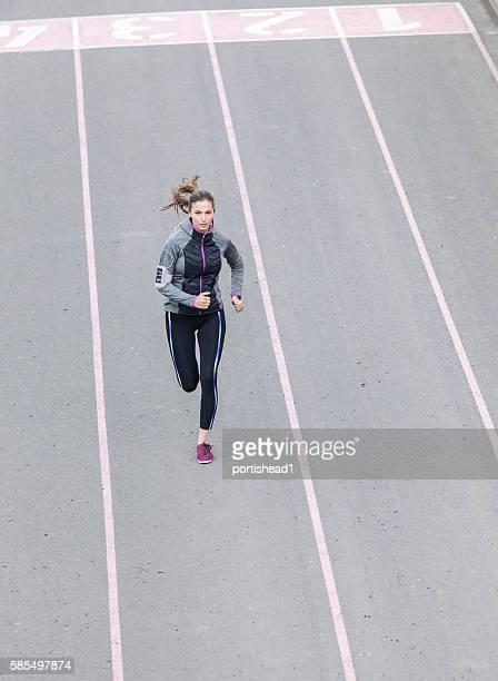 Young sportswoman running on sport track