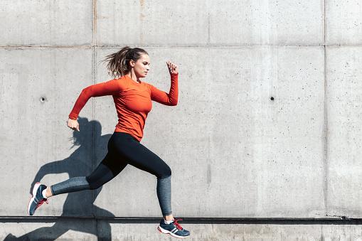 young sportswoman running outdoors 1043725924