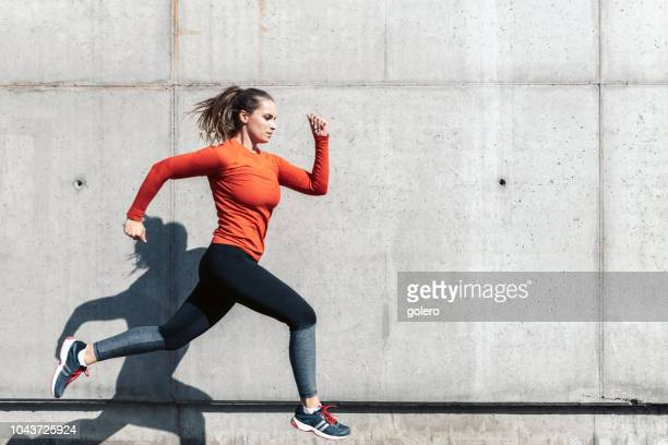 young sportswoman running outdoors - athleticism stock pictures, royalty-free photos & images