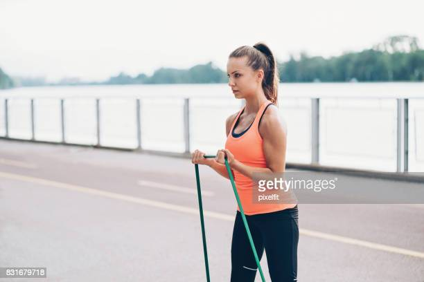 Young sportswoman stretching a resistance band
