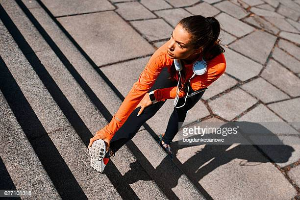 Young sportswoman stretching after cardio session