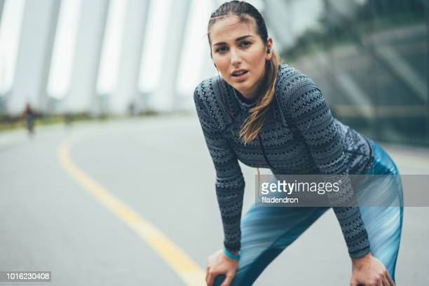 young sportswoman taking breath - sports clothing stock pictures, royalty-free photos & images