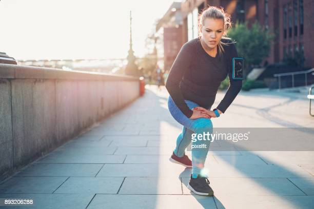young sportswoman warming up outdoors - chubby legs stock photos and pictures