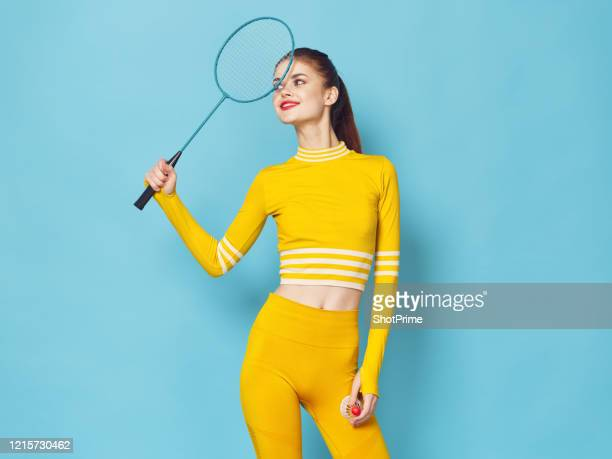 young sportswoman with badminton racket and shuttlecock in hands in a bright sports suit on a blue background. - world sports championship stock pictures, royalty-free photos & images