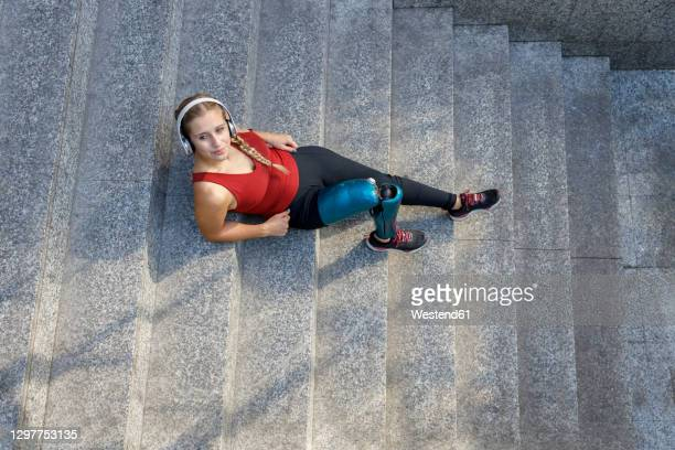 young sportswoman with prosthetic leg relaxing while sitting on steps - leaning disability stock pictures, royalty-free photos & images