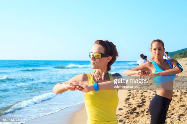 Junge Sportler Strecken am Strand