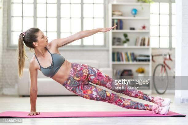 若いスポーティーな魅力的な女性がヨガを練習し、ヴァシスタサナ運動をする - 自重トレーニング ストックフォトと画像