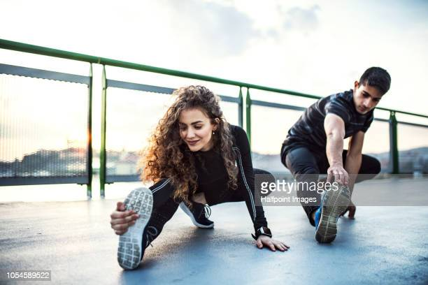 A young sporty couple stretching on a bridge outdoors in the city.