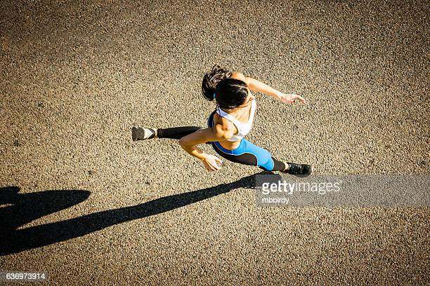young sporty looking woman running - maratona foto e immagini stock