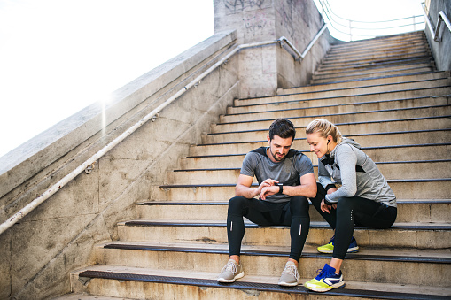 Young sporty man and woman with earphones sitting on stairs outside in a city, using smart watch. - gettyimageskorea
