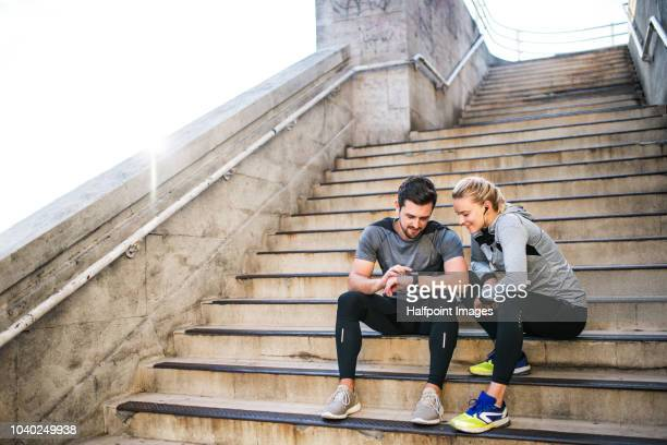 young sporty man and woman with earphones sitting on stairs outside in a city, using smart watch. - wearable computer stock pictures, royalty-free photos & images