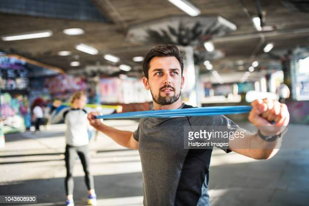 young sporty man exercising with resistance elastic bands under the bridge outside in a city. - gummi stock-fotos und bilder